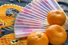 Año Nuevo chino, mandarinas y una fan que miente en la tela de seda con un dragón bordado Imagen de archivo