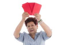 Año Nuevo chino mayor que sostiene sobres rojos en blanco Imágenes de archivo libres de regalías