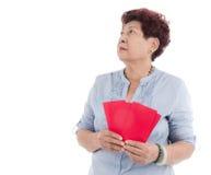Año Nuevo chino mayor que sostiene sobres rojos en blanco Foto de archivo libre de regalías