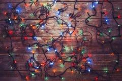 Año Nuevo colorido Garland On eléctrico una pared de madera, visión superior Fotografía de archivo