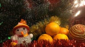Año Nuevo Composición de la Navidad de mandarines, ramas de árbol de navidad y un muñeco de nieve y bengalas Imagen de archivo libre de regalías