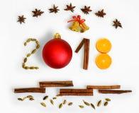 Año Nuevo 2018 3D numera con las especias, la naranja, las campanas y la bola roja en un fondo blanco Tarjeta de Navidad Imagen de archivo