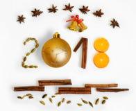 Año Nuevo 2018 3D numera con las especias, la naranja, las campanas y la bola roja en un fondo blanco Tarjeta de Navidad Foto de archivo libre de regalías