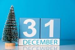 Año Nuevo 31 de diciembre día 31 del mes de diciembre, calendario con poco árbol de navidad en fondo azul Flor en la nieve Fotografía de archivo libre de regalías
