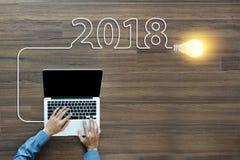 Año Nuevo de la idea 2018 de la bombilla con el trabajo en el ordenador portátil Imagenes de archivo
