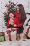 Año Nuevo de la muchacha y del niño con los presentes en manos Fotografía de archivo libre de regalías