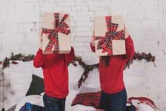 Año Nuevo de la muchacha y del niño con los presentes en manos Imágenes de archivo libres de regalías