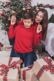 Año Nuevo de la muchacha y del niño con los presentes en manos Fotos de archivo