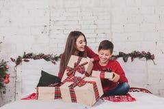Año Nuevo de la muchacha y del niño con los presentes en manos Imagenes de archivo
