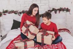 Año Nuevo de la muchacha y del niño con los presentes en manos Foto de archivo