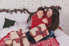 Año Nuevo de la muchacha y del niño con los presentes en manos Imagen de archivo libre de regalías