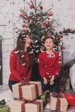 Año Nuevo de la muchacha y del niño con los presentes en manos Foto de archivo libre de regalías