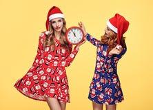 Año Nuevo de la Navidad Mujer en el sombrero de Papá Noel con el reloj Imagen de archivo libre de regalías