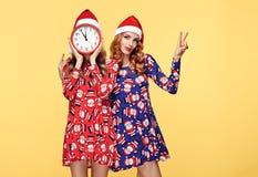 Año Nuevo de la Navidad Mujer en el sombrero de Papá Noel con el reloj Imágenes de archivo libres de regalías