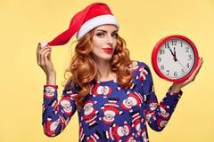 Año Nuevo de la Navidad Mujer en el sombrero de Papá Noel con el reloj Fotos de archivo libres de regalías