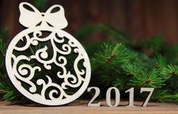 Año Nuevo 2017, decoración del árbol de navidad con una rama de un abeto y figuras de madera del año que viene, Fotografía de archivo libre de regalías