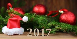 Año Nuevo 2017 Decoraciones rojas del árbol de navidad y un casquillo de la Navidad con las figuras Fotos de archivo libres de regalías