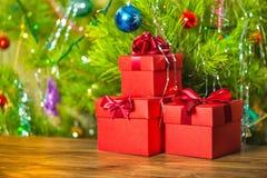 Año Nuevo del concepto de las cajas de regalo rojas con el arco en fondo de madera Imagen de archivo