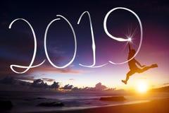 Año Nuevo 2019 el hombre que salta y que dibuja en la playa fotos de archivo libres de regalías