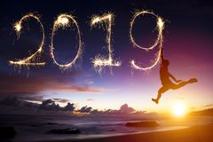 Año Nuevo 2019 el hombre que salta y que dibuja en la playa imagenes de archivo