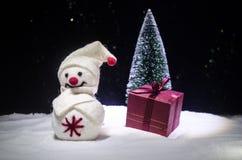 Año Nuevo El muñeco de nieve descarga los regalos por el Año Nuevo Muñeco de nieve blanco rodeado por los árboles de navidad en f Foto de archivo libre de regalías