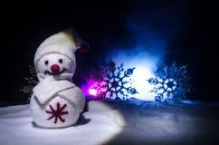Año Nuevo El muñeco de nieve descarga los regalos por el Año Nuevo Muñeco de nieve blanco rodeado por los árboles de navidad en f Imagen de archivo
