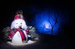 Año Nuevo El muñeco de nieve descarga los regalos por el Año Nuevo Muñeco de nieve blanco rodeado por los árboles de navidad en f Fotografía de archivo