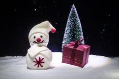 Año Nuevo El muñeco de nieve descarga los regalos por el Año Nuevo Muñeco de nieve blanco rodeado por los árboles de navidad en f Imágenes de archivo libres de regalías