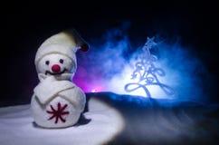 Año Nuevo El muñeco de nieve descarga los regalos por el Año Nuevo Muñeco de nieve blanco rodeado por los árboles de navidad en f Fotografía de archivo libre de regalías