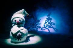 Año Nuevo El muñeco de nieve descarga los regalos por el Año Nuevo Muñeco de nieve blanco rodeado por los árboles de navidad en f Foto de archivo