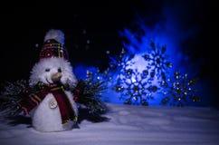 Año Nuevo El muñeco de nieve descarga los regalos por el Año Nuevo Muñeco de nieve blanco rodeado por los árboles de navidad en f Imagen de archivo libre de regalías