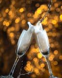 Año Nuevo en la medianoche con los vidrios del champán en fondo ligero Imagen de archivo libre de regalías