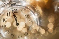 Año Nuevo en la medianoche - viejas luces del reloj y del día de fiesta Imagen de archivo