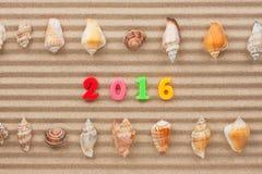 Año Nuevo 2016 escrito en la arena y la cáscara Imagenes de archivo