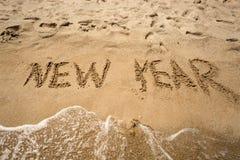 Año Nuevo escrito en la arena y que es lavado por las ondas Imágenes de archivo libres de regalías