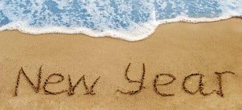 Año Nuevo escrito en una arena Imagen de archivo libre de regalías