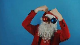 Año Nuevo, hombre como Papá Noel con los juguetes rojos y azules de las chucherías de las bolas de la Navidad, en fondo azul metrajes