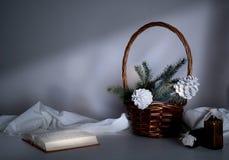 Año Nuevo, la Navidad cesta con las ramas y los conos del abeto en una tabla en el crepúsculo Fotografía de archivo