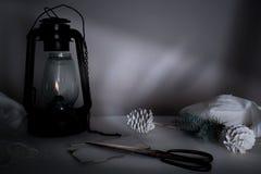 Año Nuevo, la Navidad lámpara de keroseno con las ramas y los conos del abeto en una tabla en el crepúsculo Imágenes de archivo libres de regalías
