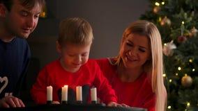 Año Nuevo, la Navidad, muchacho y madre y padre por la chimenea al lado del árbol de navidad que mira la quema metrajes