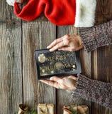 Año Nuevo, la Navidad, tableta, manos humanas, cajas de regalo, c Fotos de archivo libres de regalías