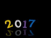 Año Nuevo 2017 Los números de madera de los niños brillantes, equilibrados, en la reflexión negra Diversión Fotos de archivo