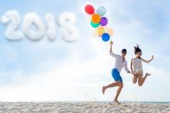 Año Nuevo 2018 Los pares sonrientes dan mantener el globo y el salto unido en la playa El amante romántico y relaja Año Nuevo Fotos de archivo libres de regalías