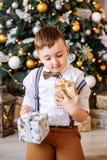 Año Nuevo Muchacho que juega cerca del árbol de navidad Imagen de archivo