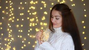 Año Nuevo Navidad La mujer hermosa en controles blancos calientes de un suéter en manos una lámpara, cierra los ojos y el sueño e almacen de video