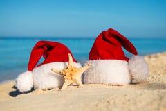 Año Nuevo romántico en el mar Vacaciones de la Navidad Sombreros de Papá Noel en la playa arenosa Fotos de archivo