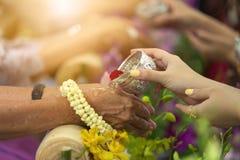 Año Nuevo tailandés - gente joven que vierte el agua y las flores en las manos del mayor en la ceremonia de Songkran Imagen de archivo