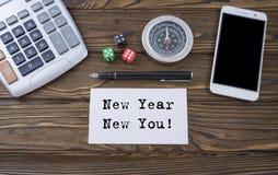 Año Nuevo nuevo usted escrito en el papel, el escritorio de madera del fondo con la calculadora, dados, el compás, el teléfono el Imagen de archivo