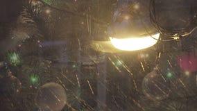 Año Nuevo Vista de una farola durante las nevadas a través del vidrio en cuál se refleja la nueva Navidad conveniente adornada metrajes