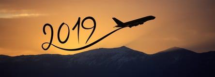 Año Nuevo 2019 volando el aeroplano en el aire en la salida del sol, bandera Foto de archivo libre de regalías